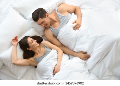 Lovely young couple resting in large bed, above view