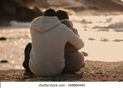 Lovely young couple sitting in front of the sea, selective focus