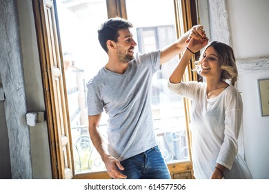 Lovely young couple smiling and dancing against window in apartment.