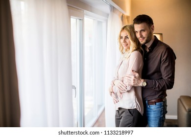 Lovely young couple standing by the window in the room