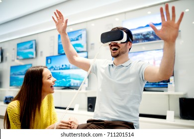 Lovely young couple is testing VR headset in the electronics store.