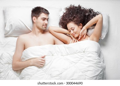 Lovely young couple waking up in bed at home. Young beautiful woman stretches her arms while man is smiling to her.