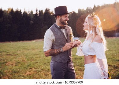 Lovely young couple in wedding dresses in Bohho style, on a field with a balloon.