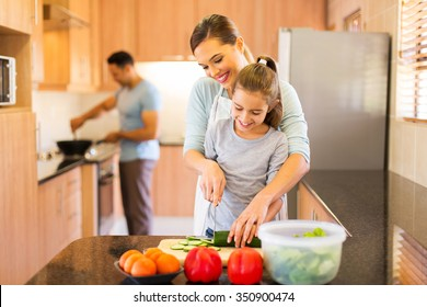 lovely young family preparing meal in kitchen