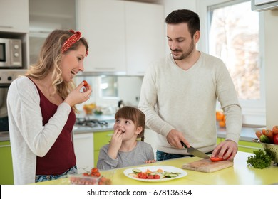 Lovely young family preparing meal in their kitchen.