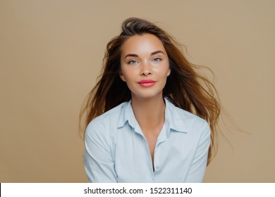 Lovely young female has long wavy hair floating in wind, dressed in elegant blue shirt, wears lipstick and makeup, poses against brown background, has direct gaze at camera, healthy facial skin
