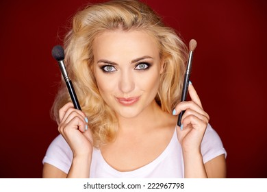 Lovely young female holding up makeup brushes with a lovely smile