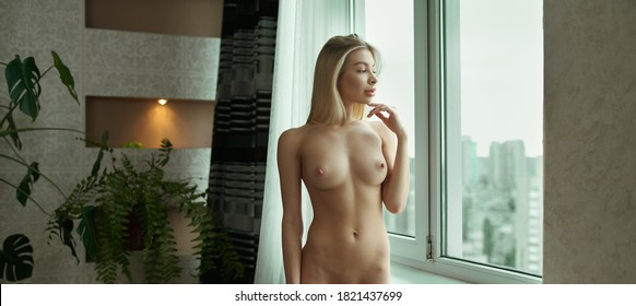 a lovely young, fully nude blonde with a beautiful, slim figure, posing gracefully and artistically by a large window in a large room. Nude young women