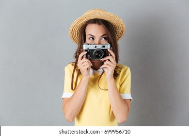 Lovely young girl in hat holding vintage camera at her face while standing isolated over gray background