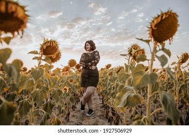 A lovely young girl laughing in a field of sunflowers on a summer day sunset