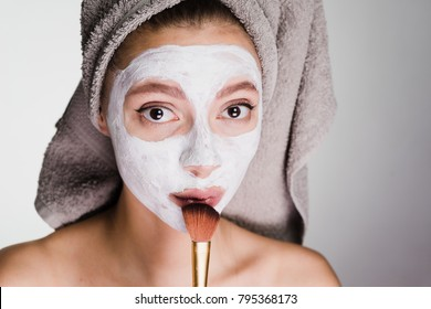 lovely young girl with a towel on her head applied a white nutritious mask on her face with a brush