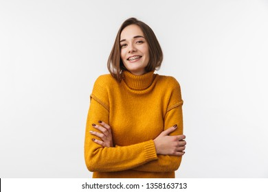 Lovely young girl wearing braces standing isolated over white background, arms folded