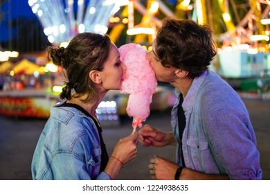 Lovely young hipster couple dating in amusment theme park. they wear jeans clothes. modern youth relationship. Ferris wheel on background