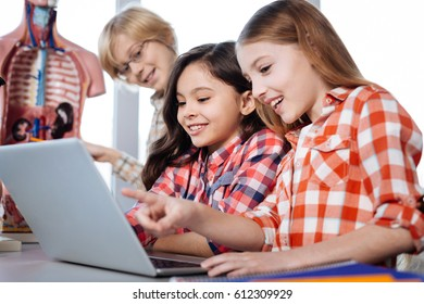Lovely young ladies reading something on laptop