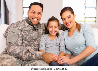 lovely young military family sitting on sofa at home