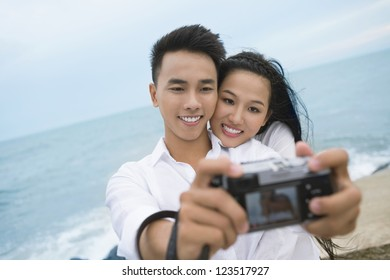 Lovely young people taking a picture of themselves with the sea in the background