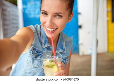 Lovely young smiling woman drinking lemonade and make a selfie.