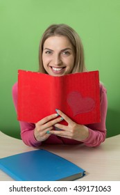 Lovely young teacher sitting at her desk and smiling into the camera