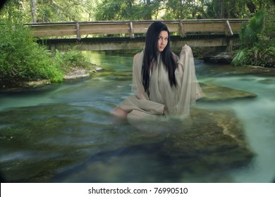 A lovely young teenage girl sits on a submerged rock, draped in sheer fabric, in a creek with crystal-clear flowing water.