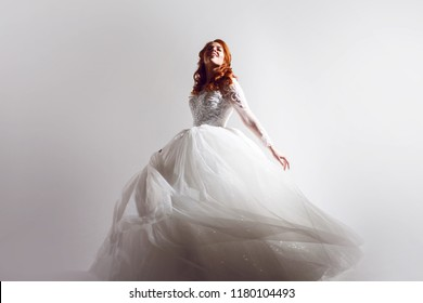 Lovely young woman bride in a lavish wedding dress. Charming bride on Light background with a shadow.Free space for some design