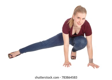 A lovely young woman crouching on the floor with one leg outstretchedin jeans and smiling, isolated for white background