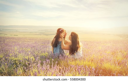 Lovely young woman and a little girl in a lavender field