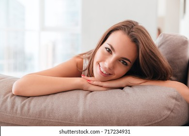 Lovely young woman lying on a pillow on a sofa at home