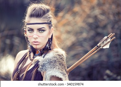 Lovely young woman with a painted face Amazon hiding in the reeds with a bow and arrows, hunting or guarding territory