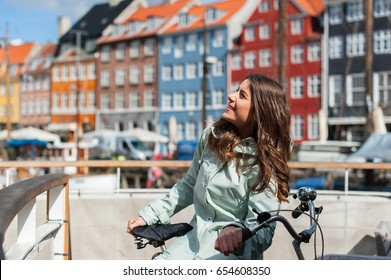 Lovely young woman posing with bike at the Nyhavn harbor pier in european city Copenhagen, Denmark, on sunny day. Visiting Scandinavia, famous European place.