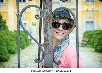 Lovely young woman posing in heart shaped gate, Marchegg castle, Austria. Female portrait. Travelling theme.