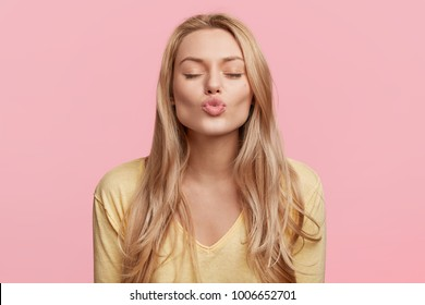Lovely young woman with rounded lips and shut eyes, makes kiss, has long blonde hair, poses against pink background, being pleased, expresses her positive feeling, imagines something pleasant