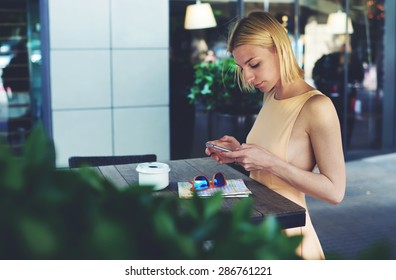 Lovely young woman sending text message with her mobile phone, sexy hipster girl chatting on cell phone standing at coffee shop, female tourist connecting to wireless on telephone for navigation