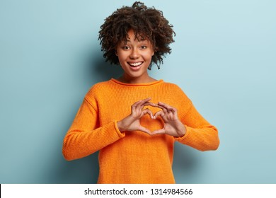 Lovely young woman shows heart symbol with both hands, smiles broadly, dressed in orange jumper, being in romantic mood, isolated over blue background, expresses love and sympathy. Body language