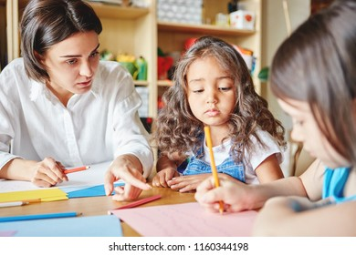 Lovely young woman sitting at table and helping adorable girls with drawing while teaching in art school