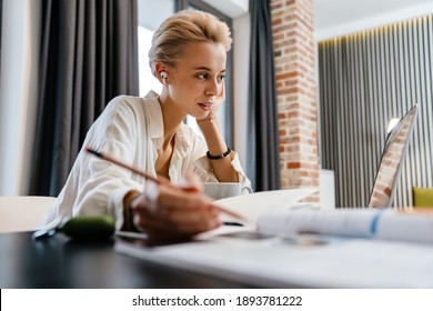 Lovely young woman studying online while sitting at the table at home, wearing earphones