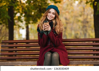 Lovely young woman wearing coat and beret sitting on bench outdoors, drinking takeaway coffee