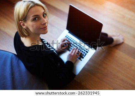 Lovely young woman working on laptop computer at home, attractive blonde hair student using laptop in her living room and look to the camera, female freelancer working at home