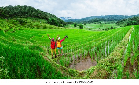 Lover asian man asian women travel nature Travel relax Walking a photo on the rice field in rainy season in Chiang Mai, Thailand