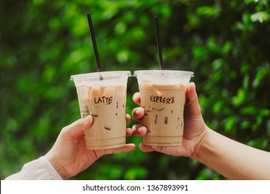 Lover couple hands holding and showing a glass cup of ice coffee latte and ice espresso outdoors on green leaf background.Vintage film tone.