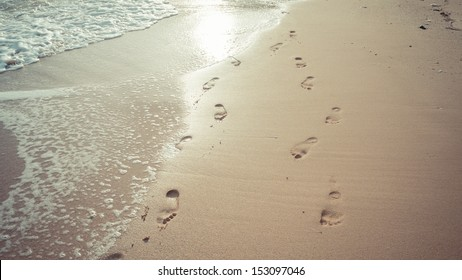 Lover footprints on the beach at sunset time in vintage style