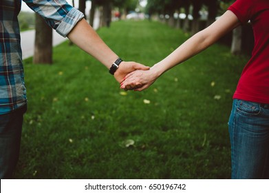 Lover hands hold together in the beautiful garden. Romantic lover theme outdoor.