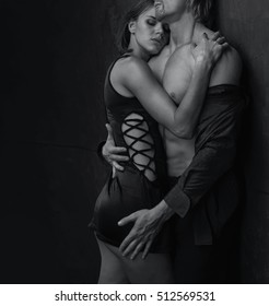 Lover sexy couple. Man and woman together  standing on a stone wall background. Love relationship in a pair. Images of the novel about love. Female dream, male instinct - passionate kissing, hugs.
