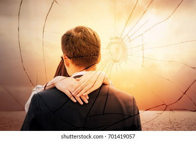 Lovers back hugging over dramatic sunset sky background.Sad young couple in relationship difficulties. Broken heart or divorce concept, double exposure. Break off, withdraw, disengage one's engagement