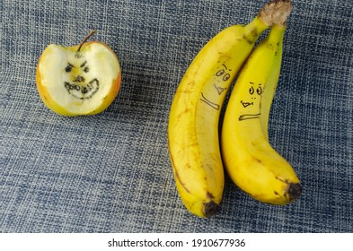 Lovers bananas and a bitten apple on white and blue background. Two ripe bananas and an apple with drawn faces. Love, relationships, family. Selective focus.