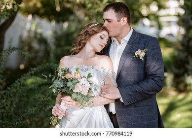Lovers of beautiful couple hugging each other. Beautiful bride in a white magnificent dress holding a bouquet of fluffy. The groom embraces the bride. dark-haired bride with ornaments in her hair