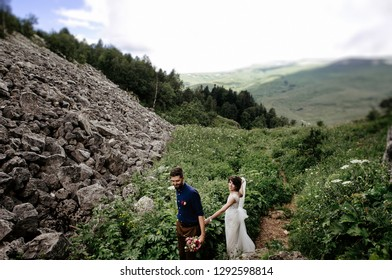 lovers - a bride in a dress and a groom in a blue shirt are dancing and walking on the top of a mountain in the summer, wedding photo for Valentine's Day
