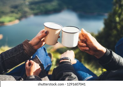 lovers couple hold in hands mug of hot drink, enjoy together of sun flare mountain, travelers drink tea on cup on nature, romantic weekend concept on background of panoramic landscape