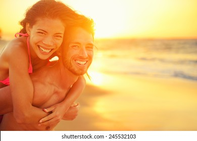 Lovers couple in love having fun dating on beach portrait. Beautiful healthy young adults girlfriend piggybacking on boyfriend hugging happy. Multiracial dating or healthy relationship concept.