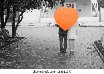 Lovers couple on a black and white photo of an orange umbrella. Rear view.