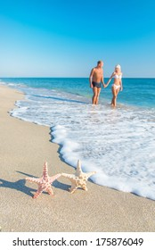 Lovers couple at sandy sea beach with  starfishes - hot countries traveling concept